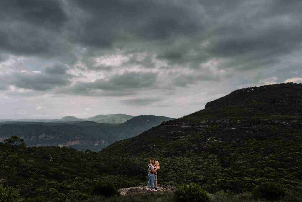 amazing top engagement photoshoot location bride and groom embracing on cliffs edge, similar to Grand Canyon elopements