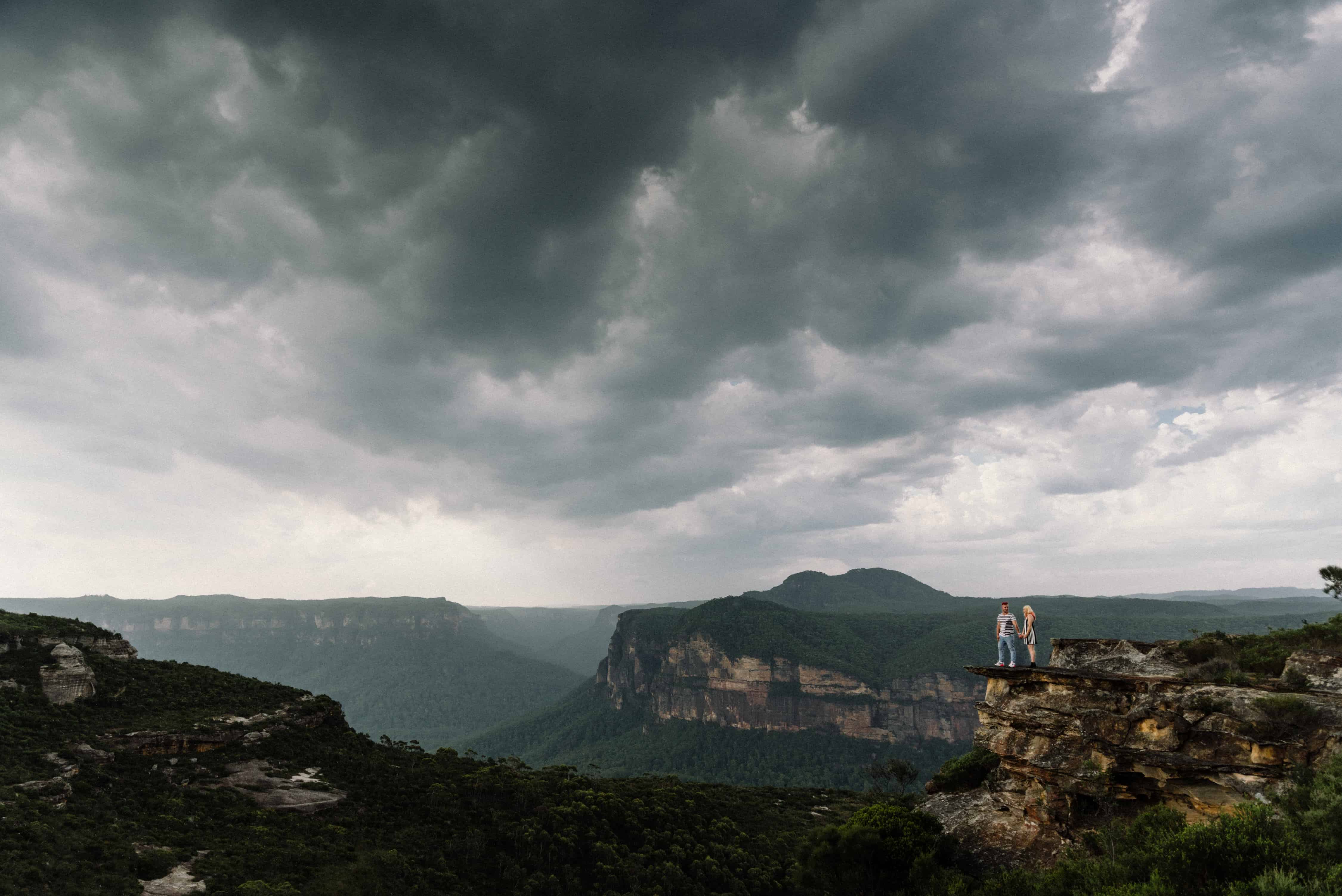 top engagement photoshoot location bride and groom with bride and groom standing on ledge as storm rolls in