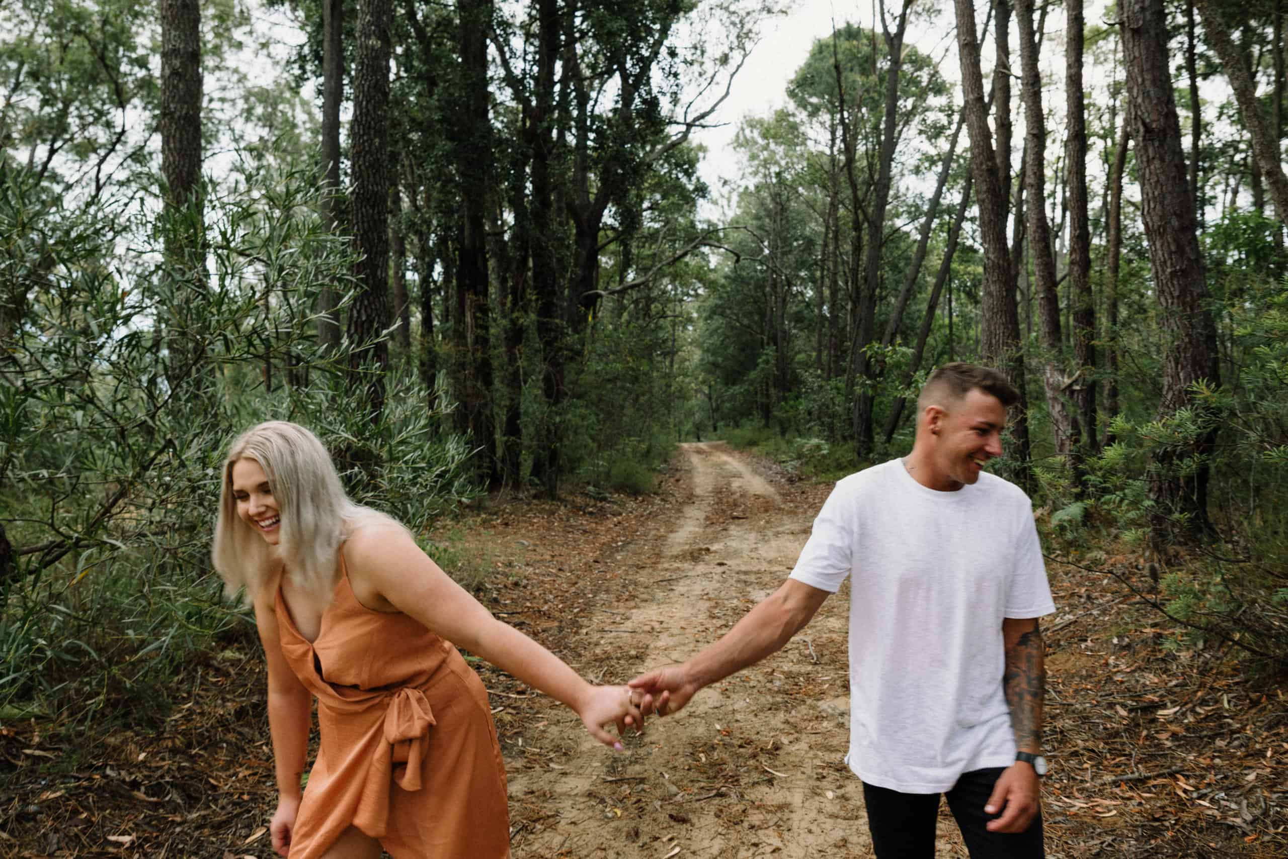 top engagement photoshoot location bride and groom standing on dirt road, laughing and holding hands
