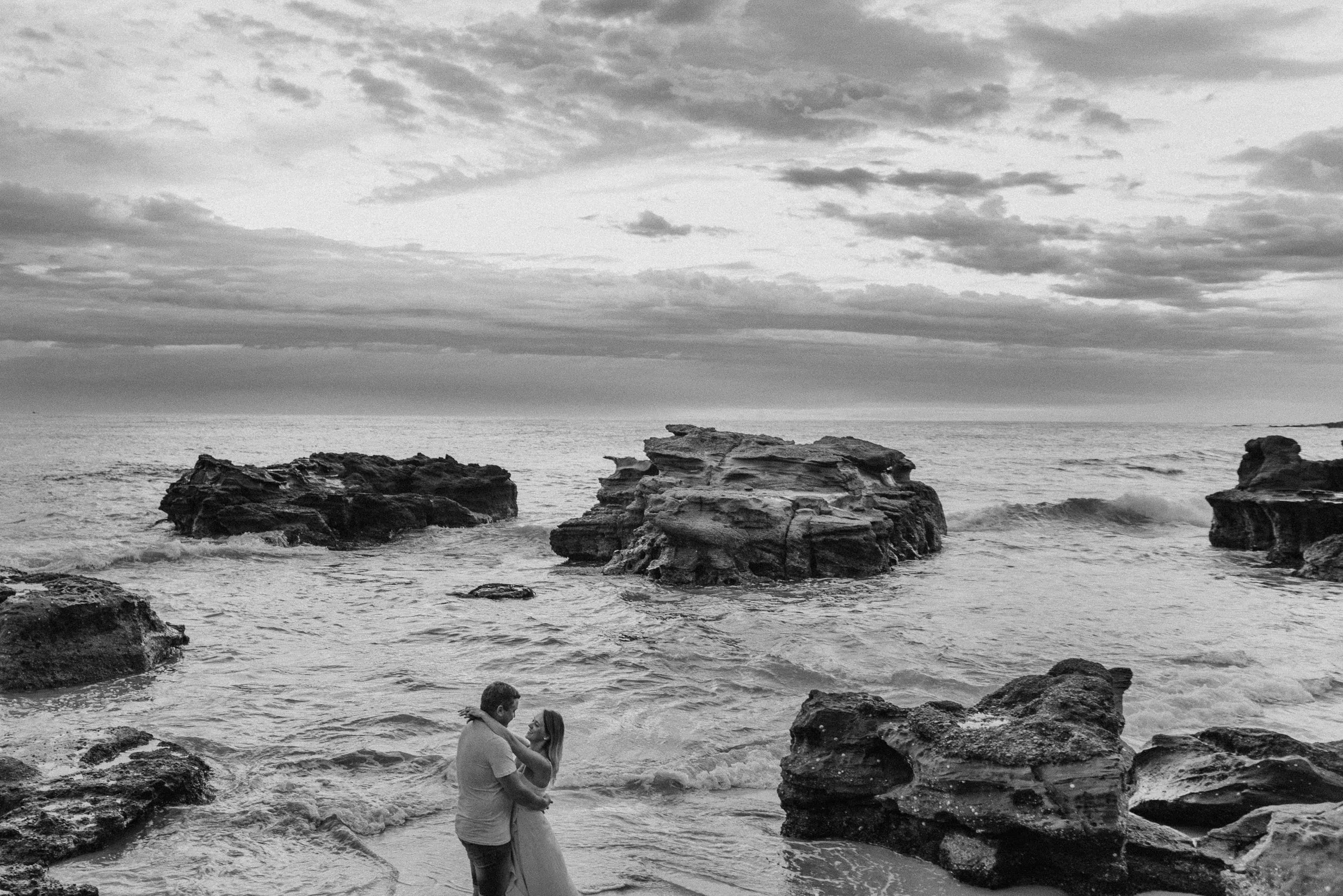 top engagement photoshoot location bride and groom embracing at caves beach in the sunrise sun