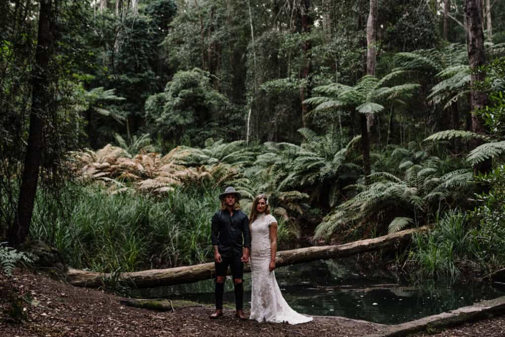 bride and groom stand deep inside a rainforest during wedding portraits
