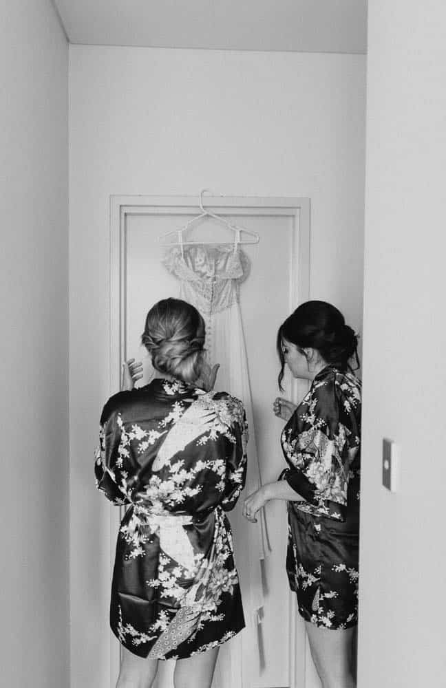 Bridesmaids helping get brides wedding dress ready captured by hunter valley wedding photographer james white