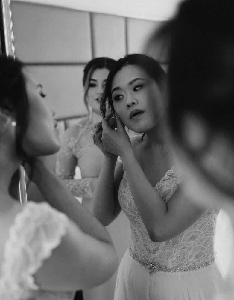 bride putting on earrings in the mirror with help of bridesmaids captured by hunter valley wedding photographer james white