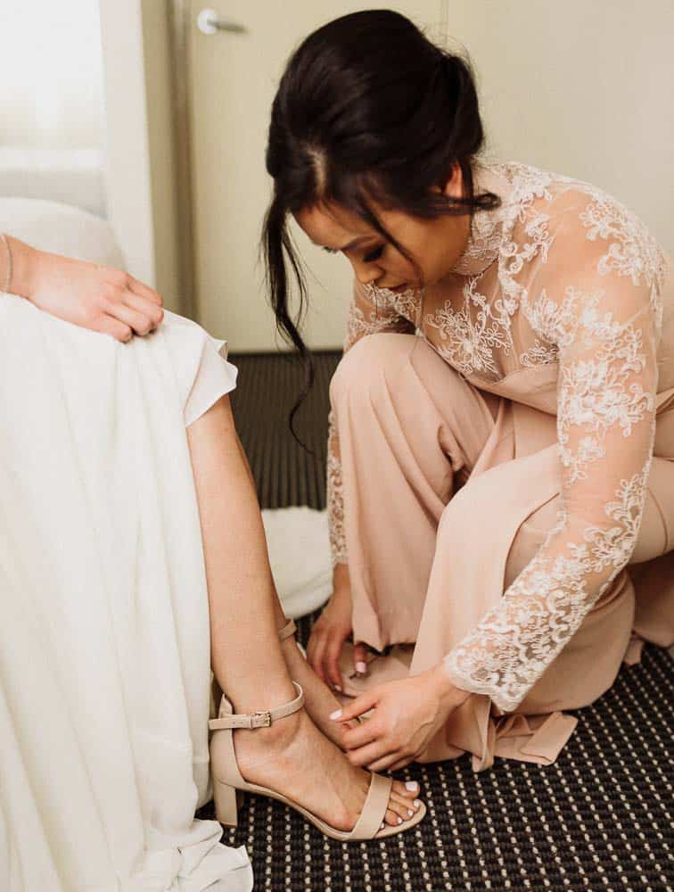 Brides sister kneeling down to put shoes on brides foot captured by hunter valley wedding photographer james white