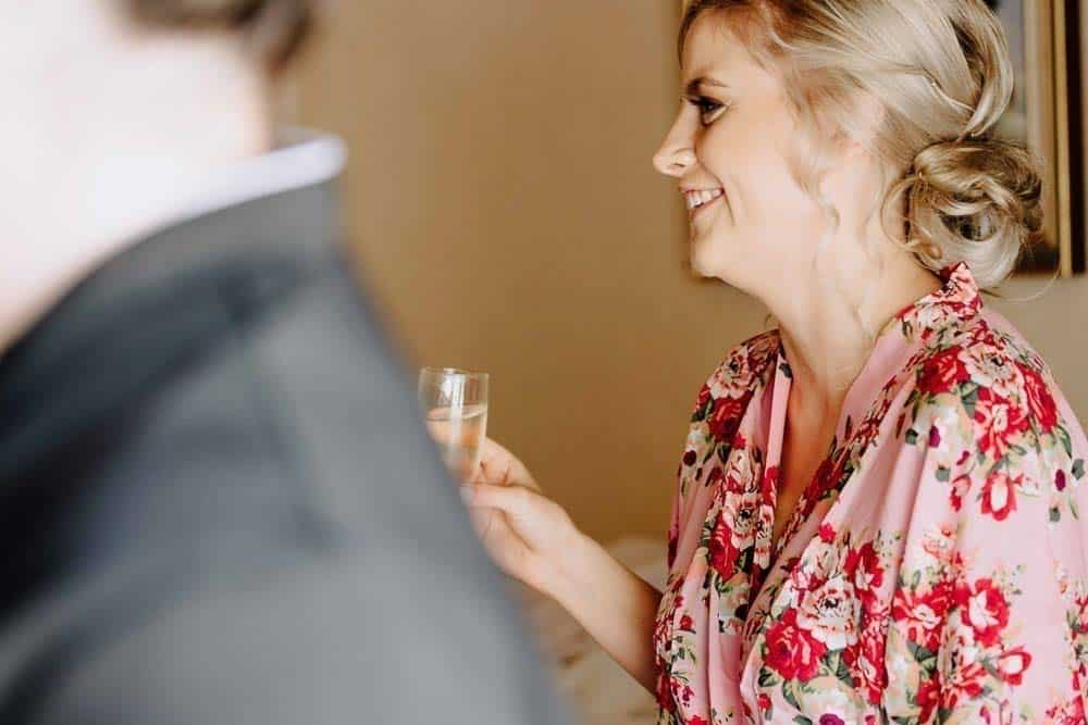 ravishing bridesmaid sips champagne during hair and makeup captured by James White Hunter Valley Wedding Photographer