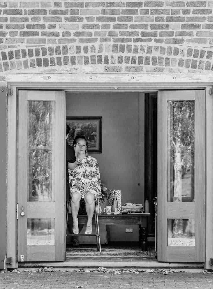 bride sits in doorway to cottage, getting hair done captured by James White Hunter Valley Wedding Photographer