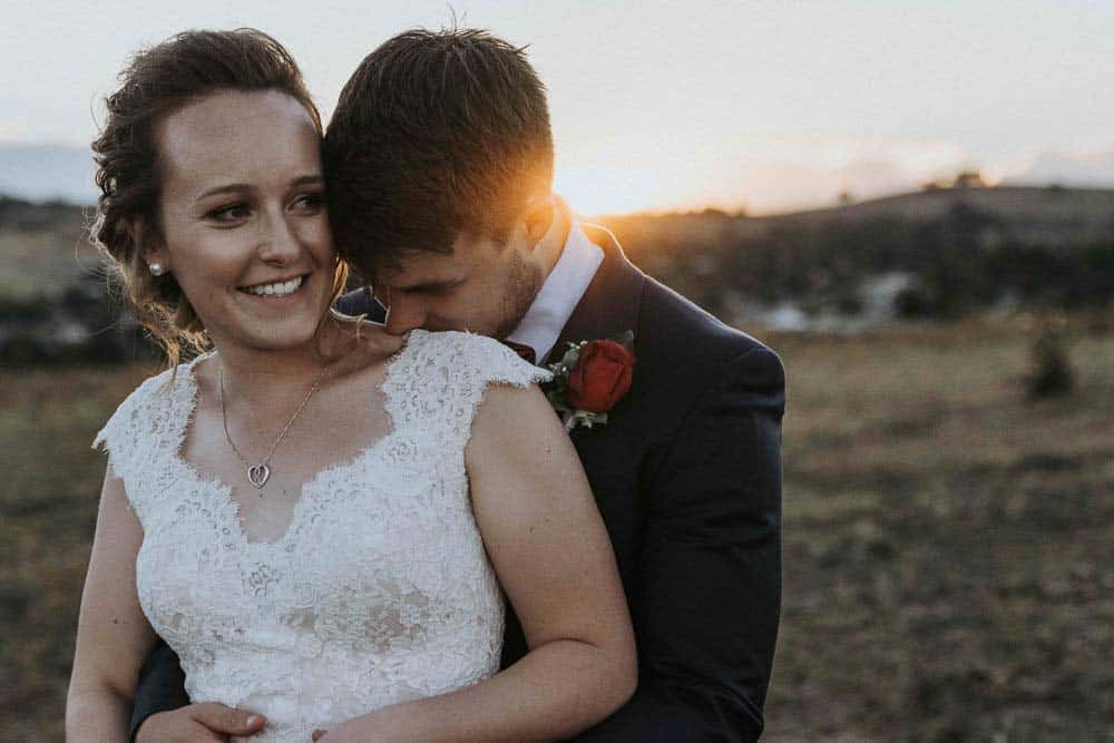 groom whispers sweet nothings in brides ears at sunset as captured by james white hunter valley wedding photographer