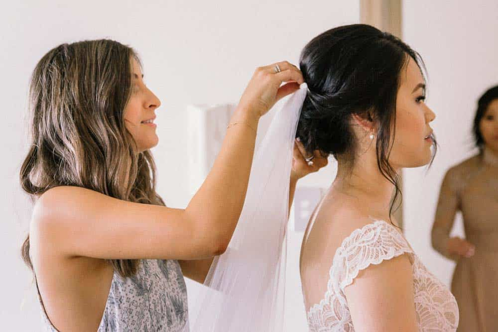 hair and makeup artist helping to put veil on bride captured by hunter valley wedding photographer james white