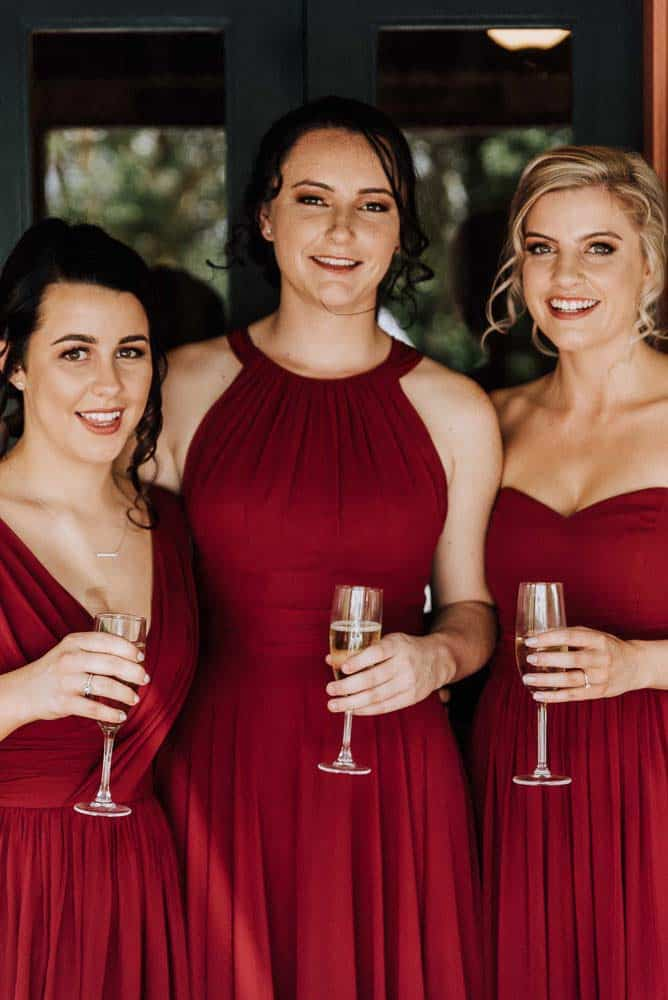 bridesmaids dressed in stunning red dresses drinking champagne captured by James White Hunter Valley Wedding Photographer