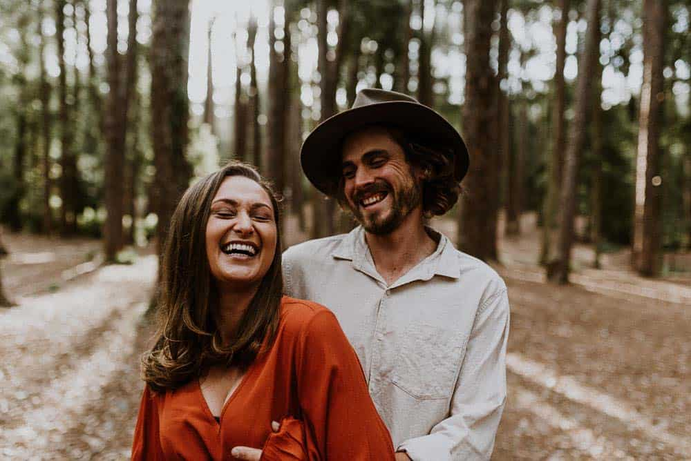 bride and groom to be laughing in forest candid shot captured by james white hunter valley wedding photographer