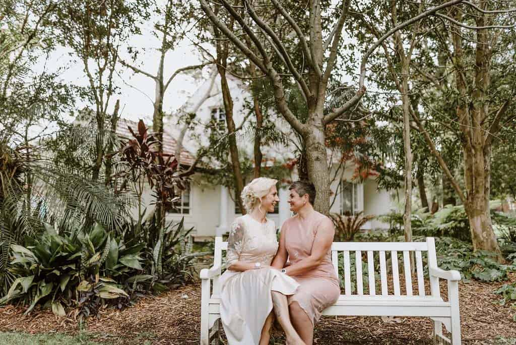 two brides sitting on park bench at wedding captured by james white hunter valley wedding photographer