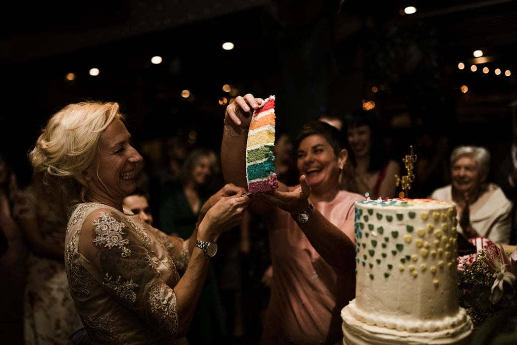 two brides cut rainbow coloured wedding cake captured by james white hunter valley wedding photographer