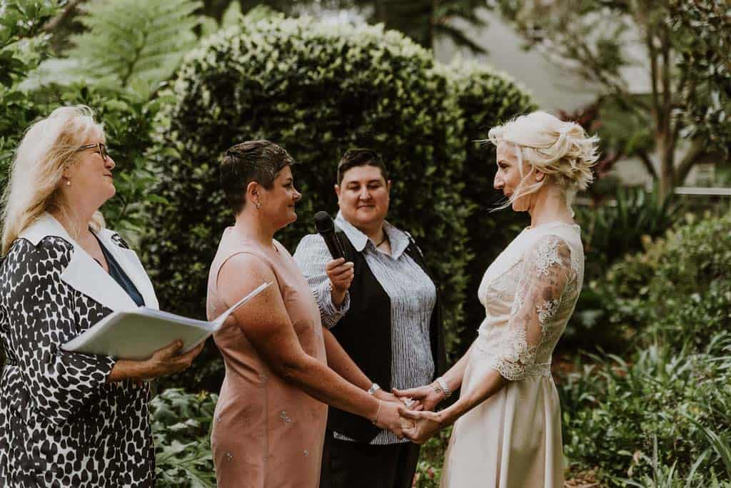 two brides hold hands at alter captured by james white hunter valley wedding photographer