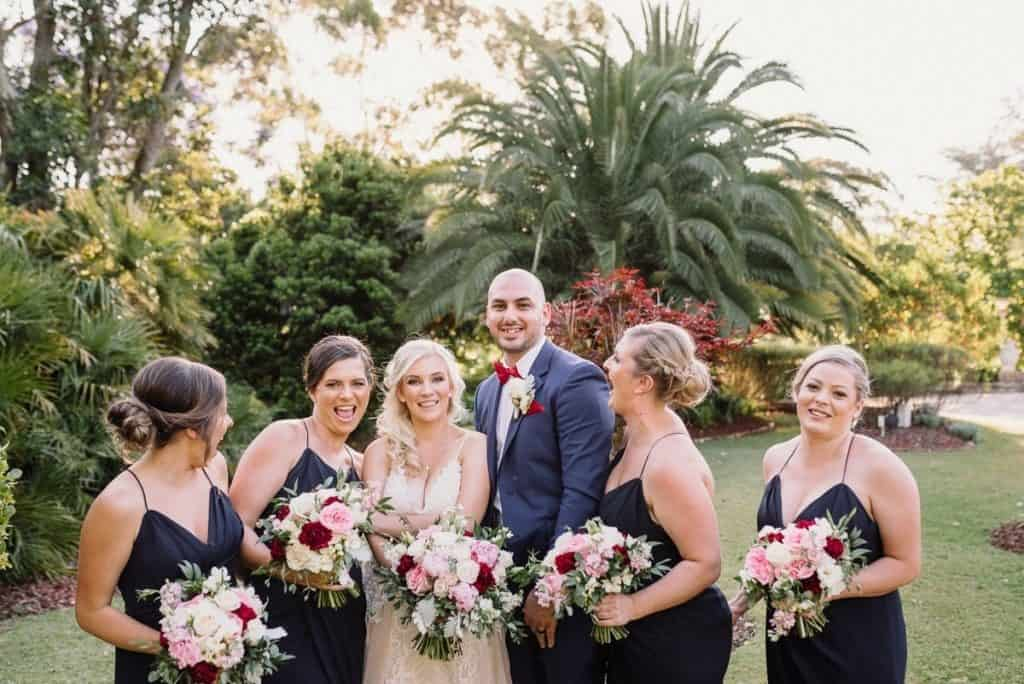 bride and groom with bridesmaids being silly and laughing captured by hunter valley wedding photographer james white