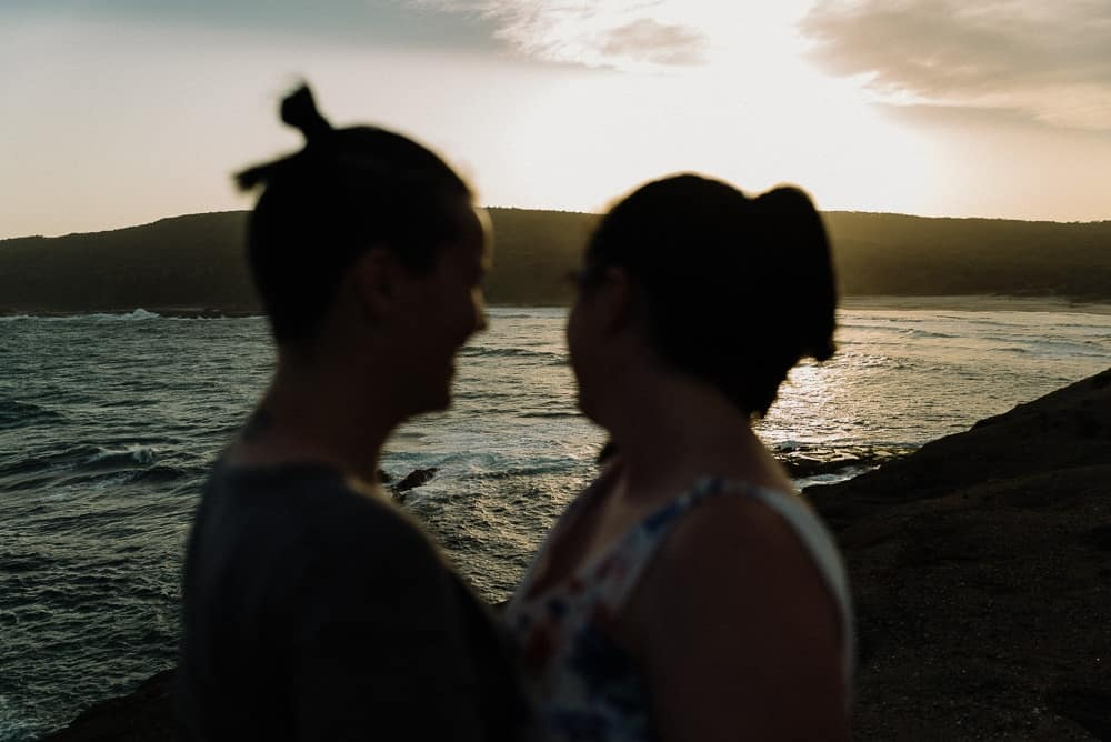 silhouette of two brides kissing on beach at sunset captured by hunter valley wedding photographer james white