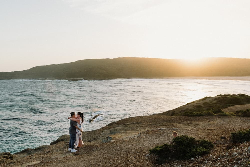 panoramic shot of brides kissing under beach sunset captured by hunter valley wedding photographer james white