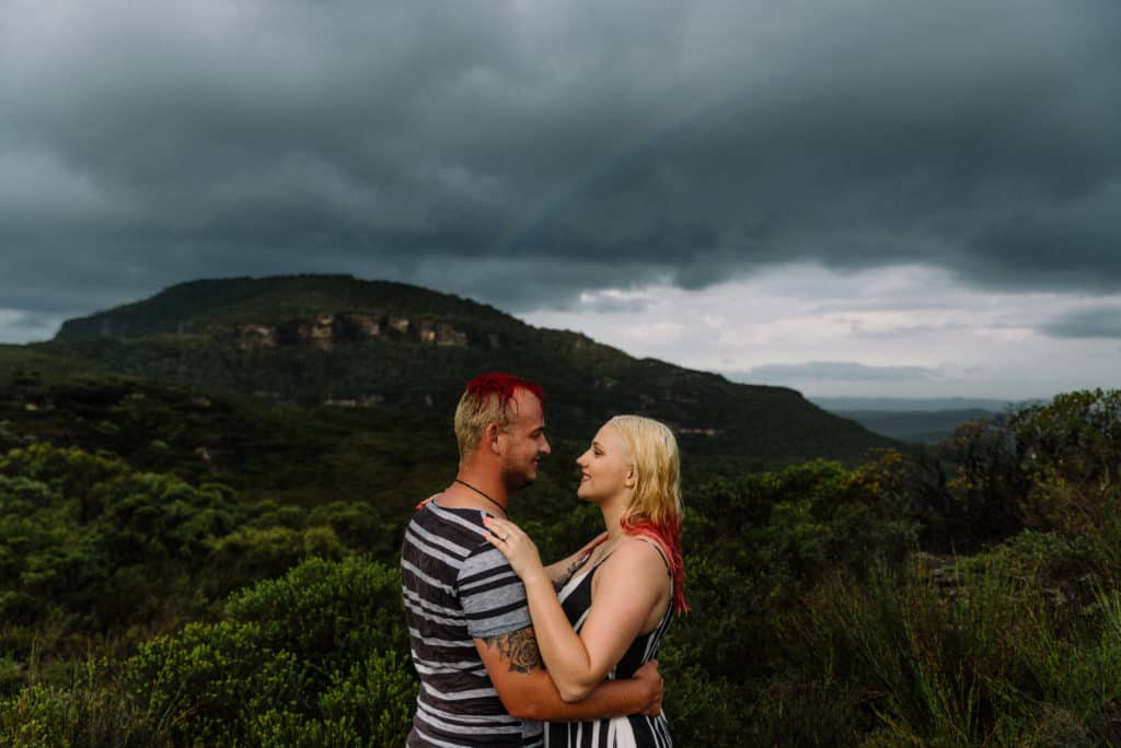 bride and groom standing in the rain, kissing on a mountain during pre-wedding photoshoot. captured by james white hunter valley wedding photographer