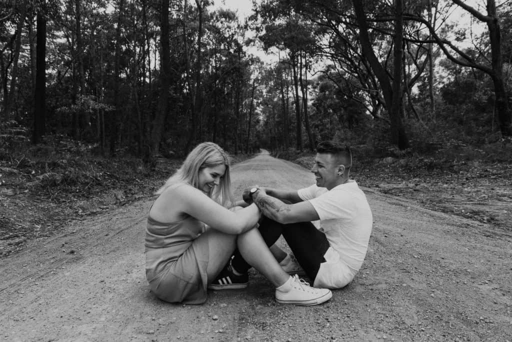 bride and groom sit in middle of road in the rain captured by hunter valley wedding photographer james white