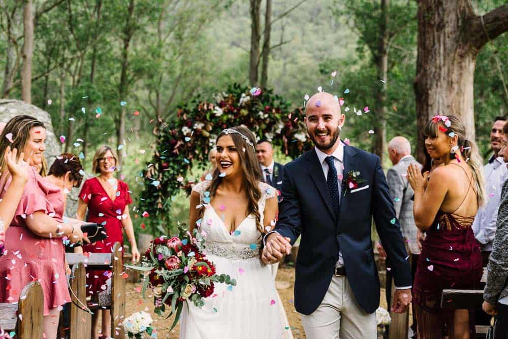 mystwood bride and groom walk down the aisle, confetti thrown on them