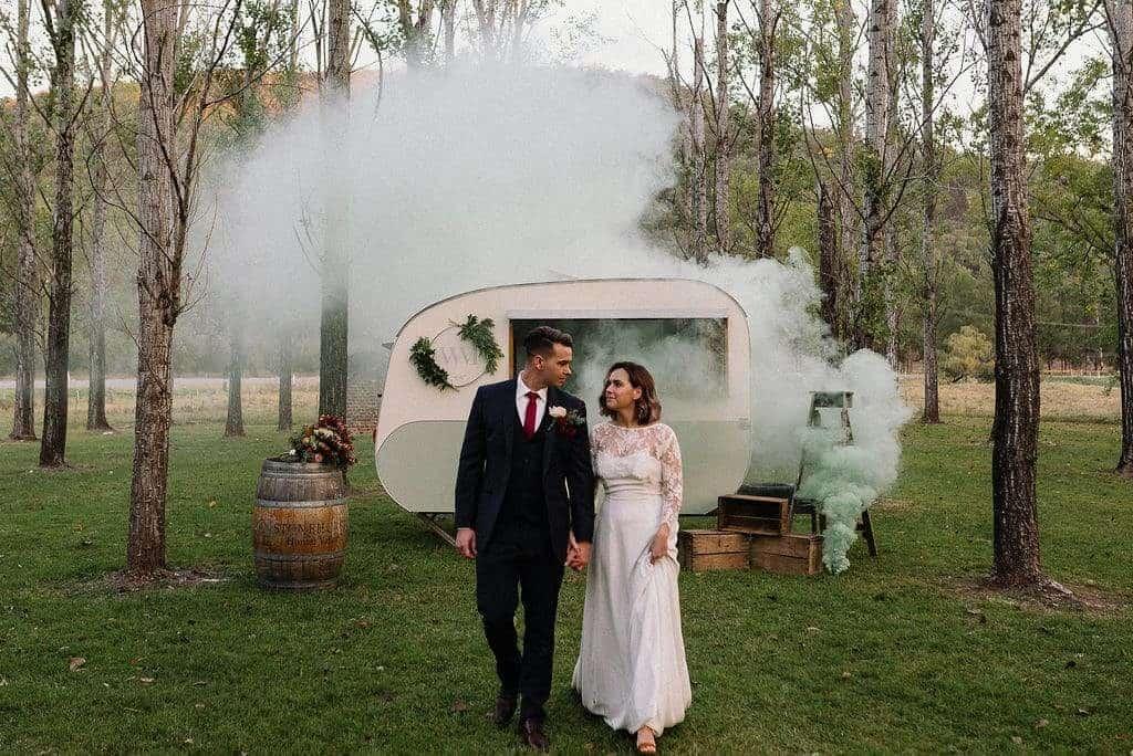 bride and groom at stonehurst cedar creek, walking between trees