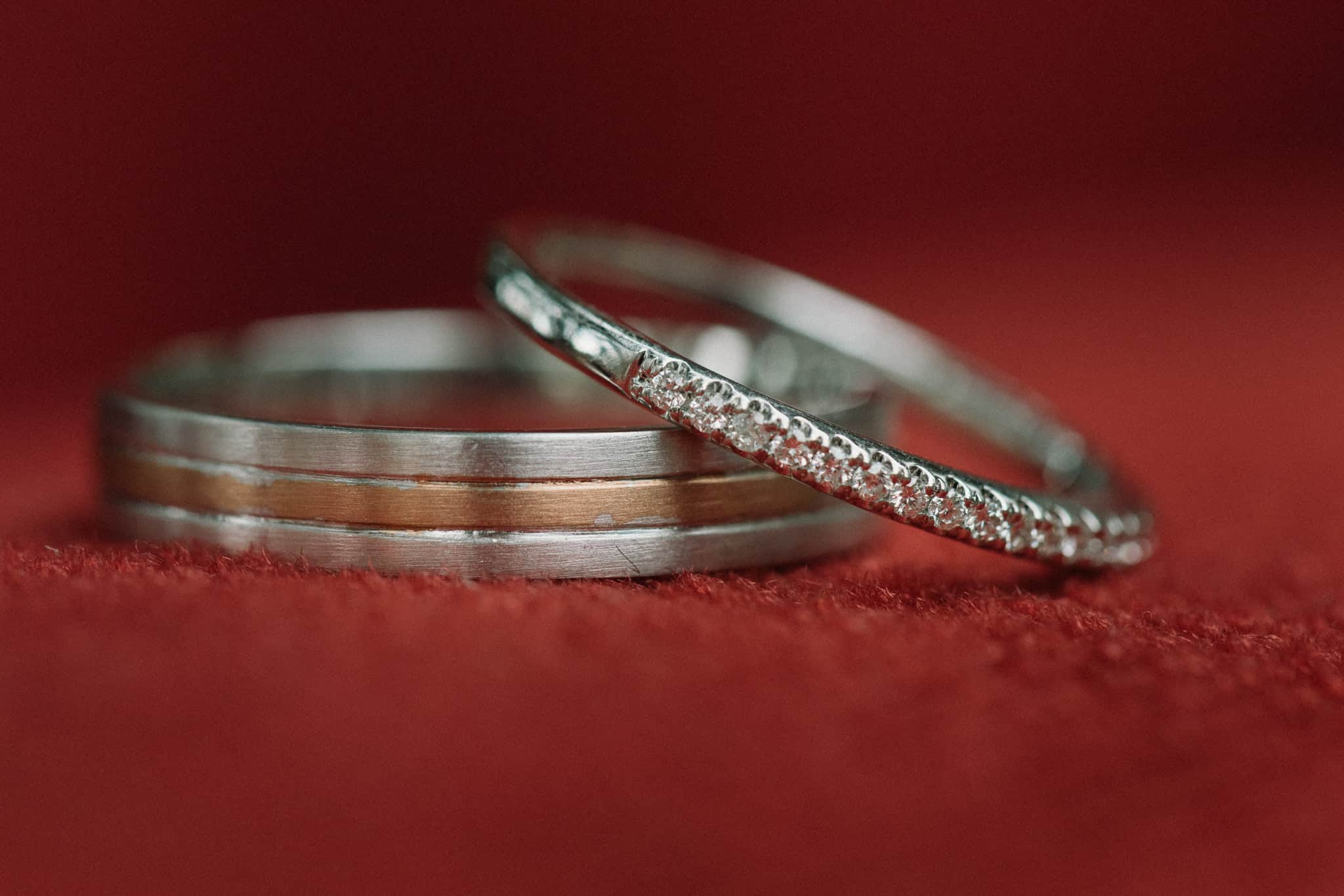 bride and groom rings sitting on red velvet cushion Captured by James White Hunter Valley Wedding Photographer
