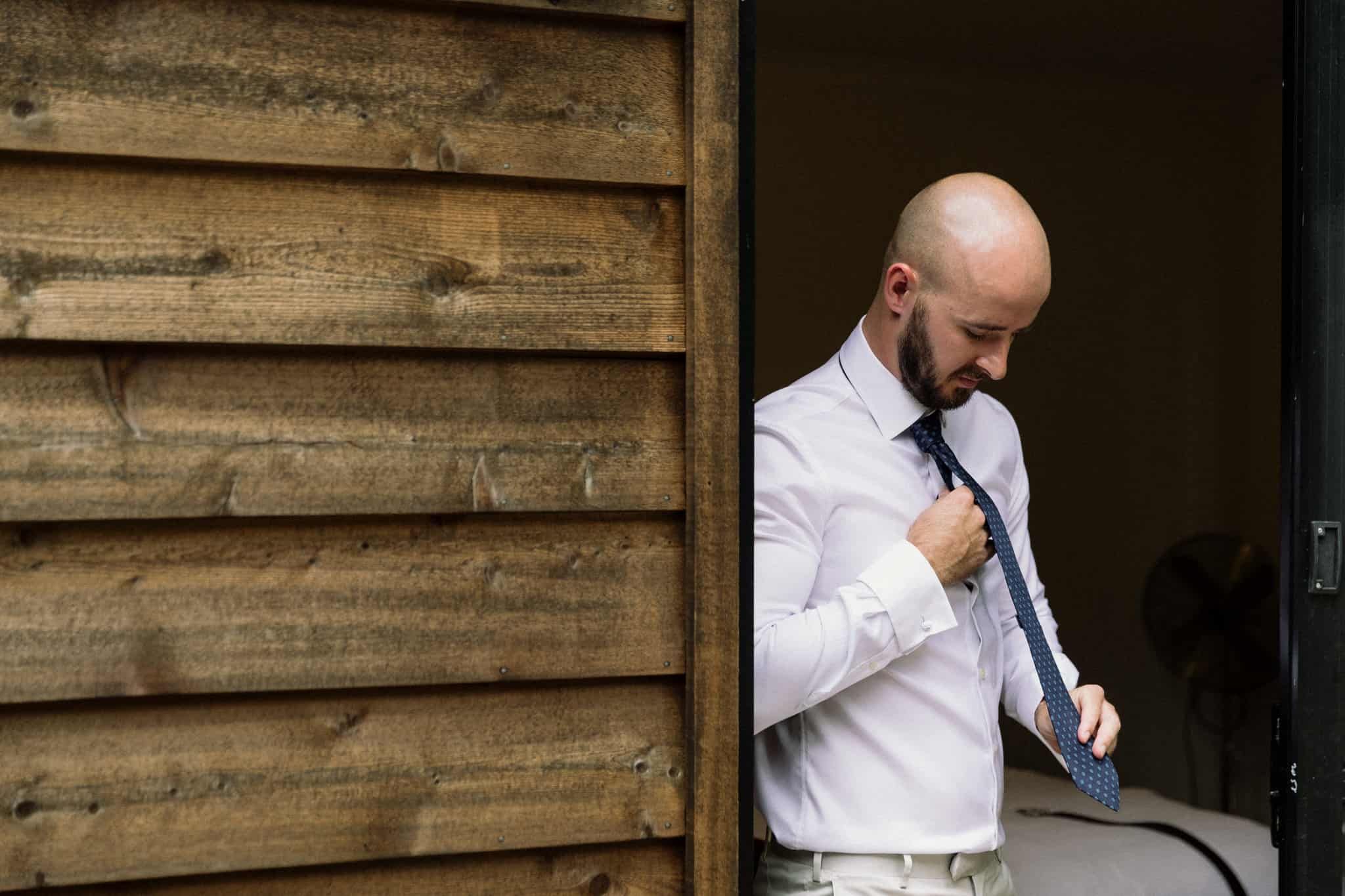 Groom getting ready inside cabin doing tie Captured by James White Hunter Valley Wedding Photographer