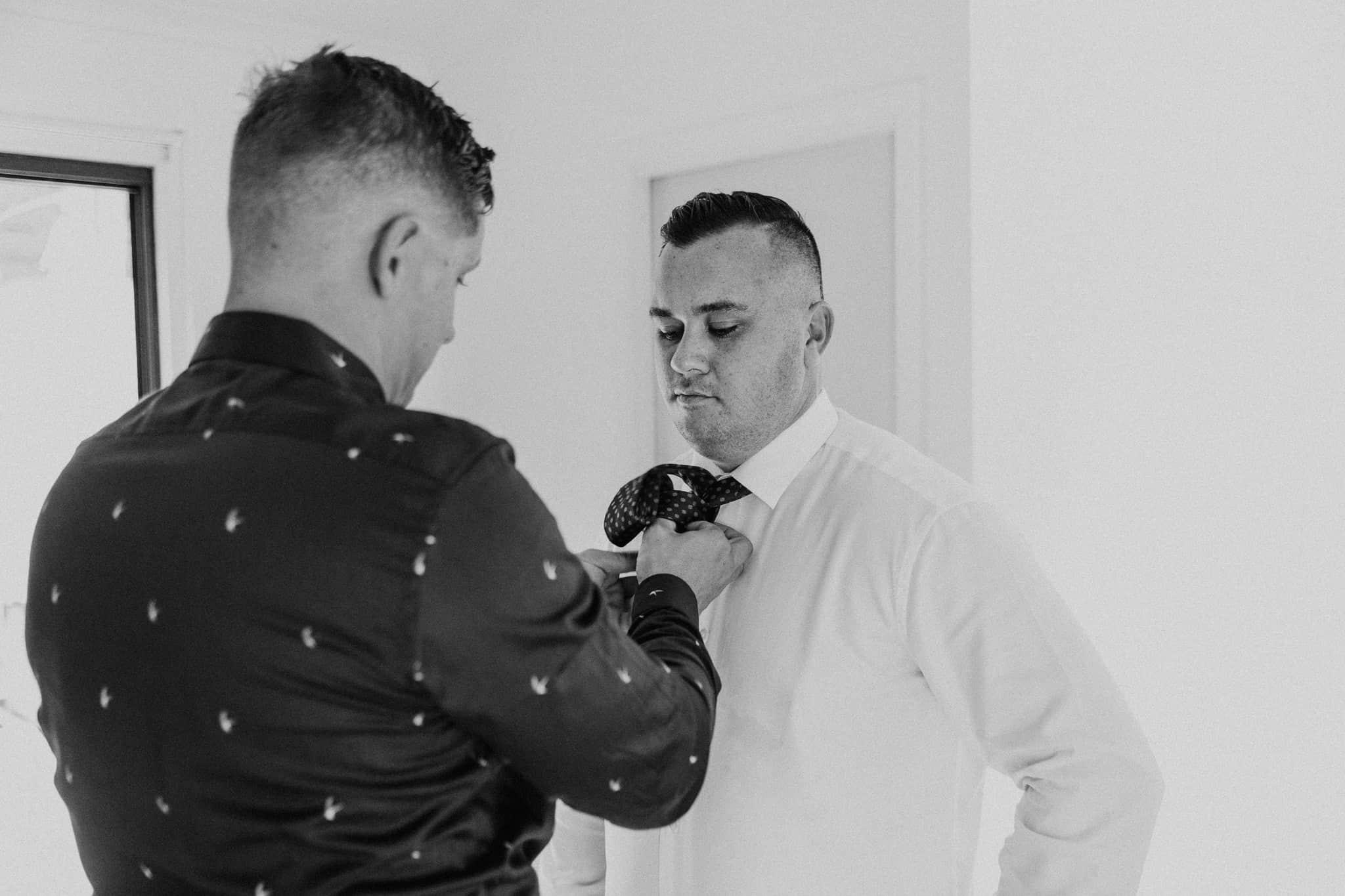 Groomsmen helps do tie Captured by James White Hunter Valley Wedding Photographer