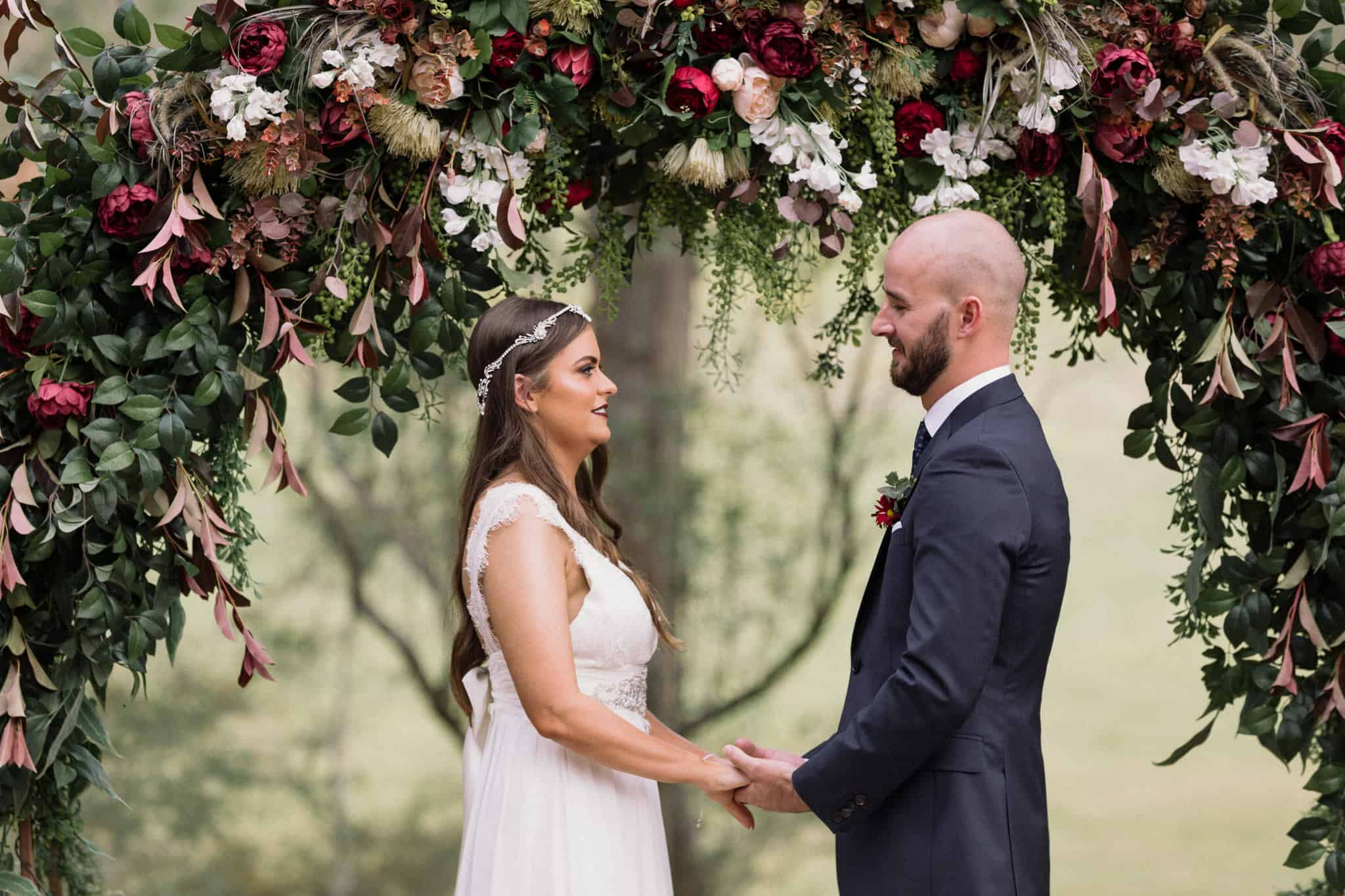 Bride and groom hold hands in front of large floral display at ceremony Captured by James White Hunter Valley Wedding Photographer