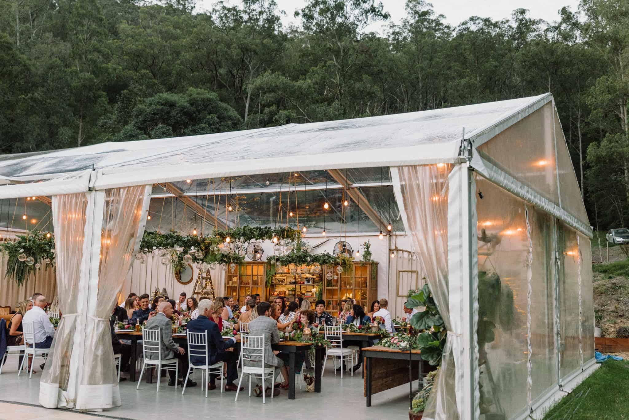 Guests sit down inside marquee at whimsical boho styled reception Captured by James White Hunter Valley Wedding Photographer