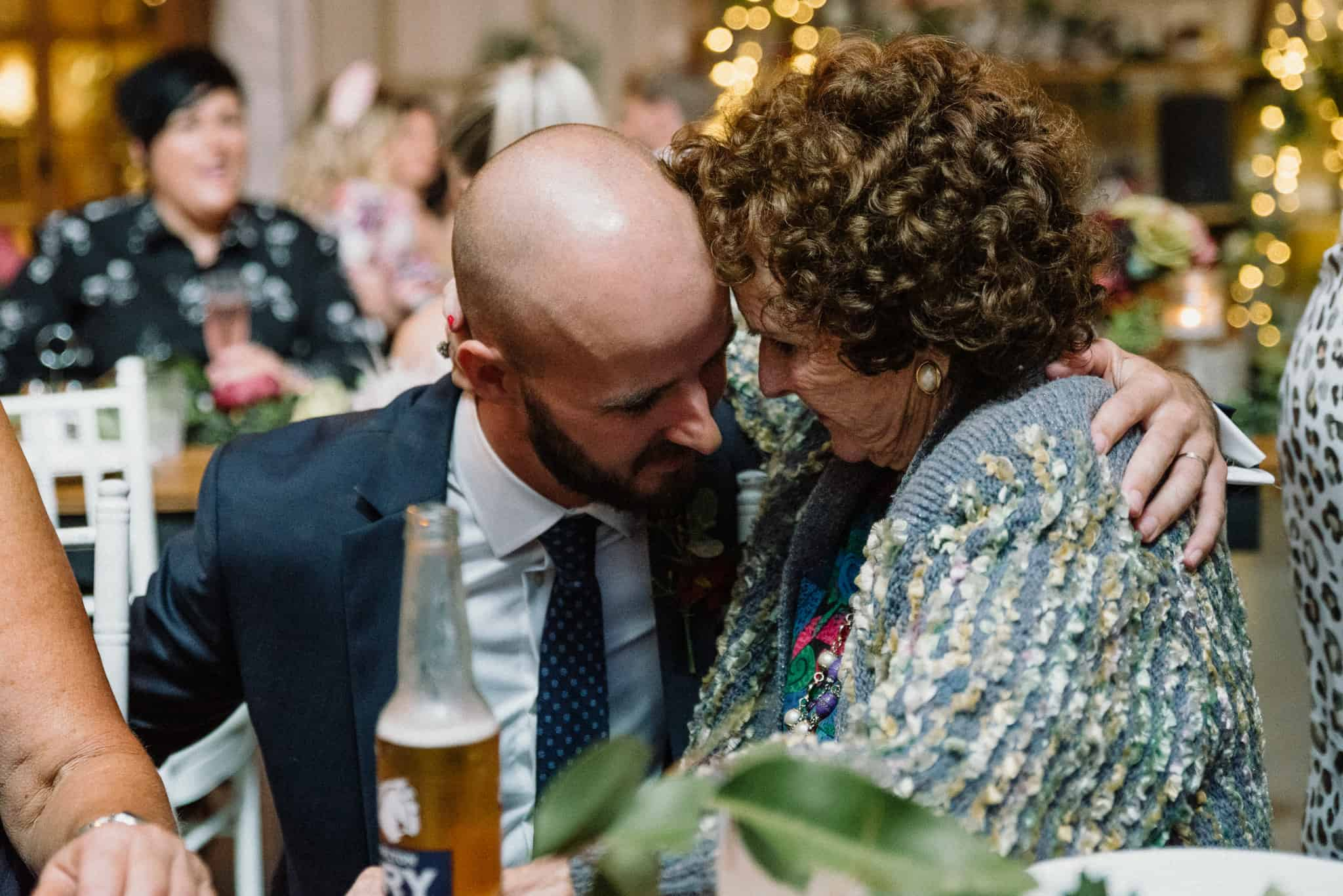 Groom shares moment with elderly guest during reception Captured by James White Hunter Valley Wedding Photographer