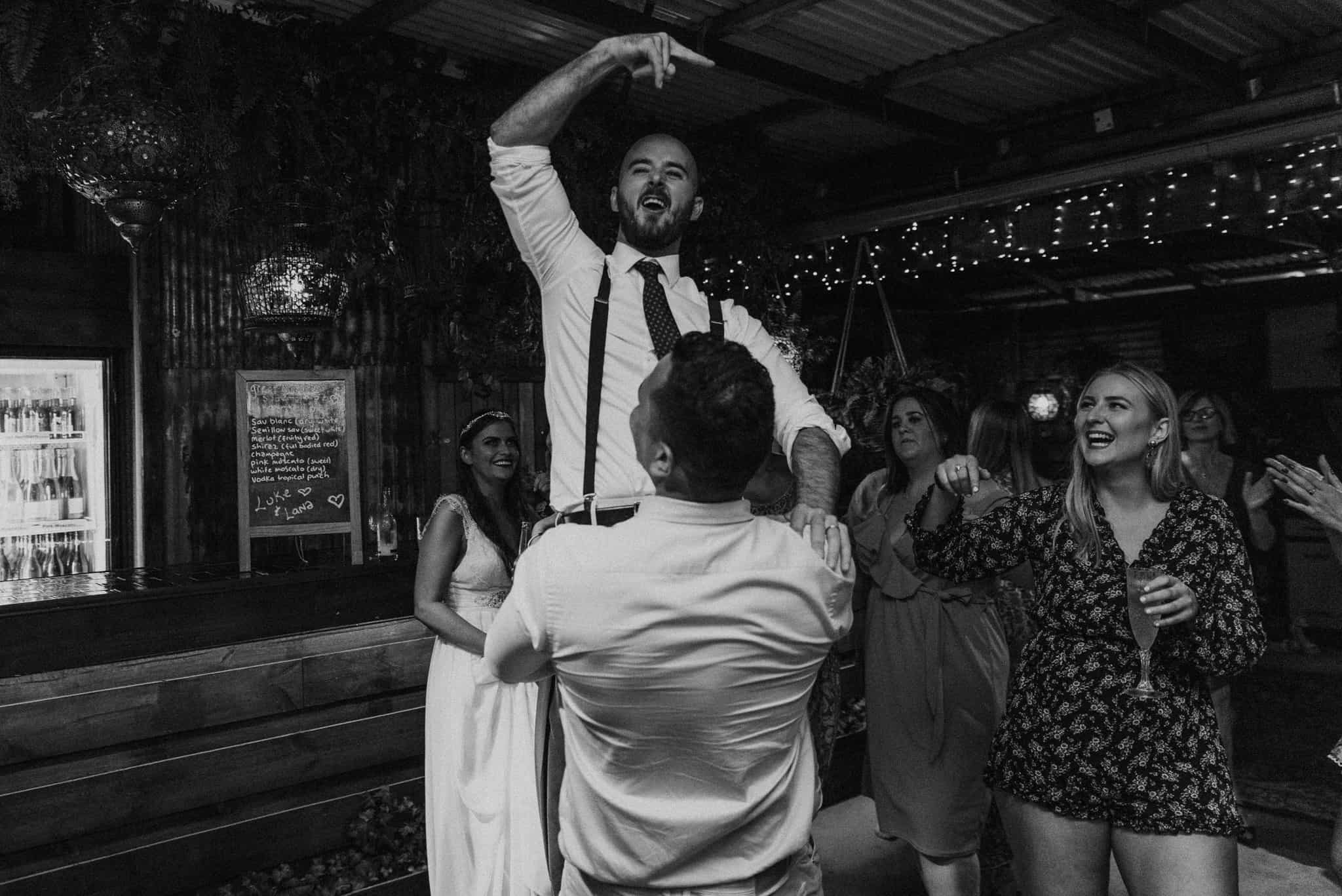 Groomsman lifts up groom for dance Captured by James White Hunter Valley Wedding Photographer