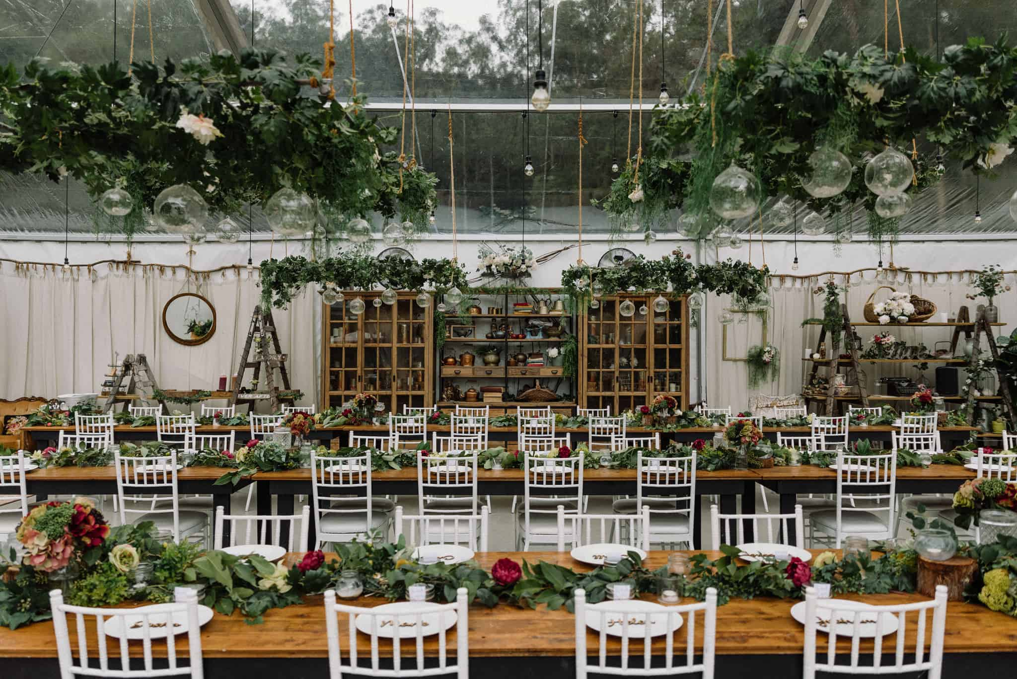 Rustic whimsical wedding reception setup with hanging greenery and wooden tables Captured by James White Hunter Valley Wedding Photographer