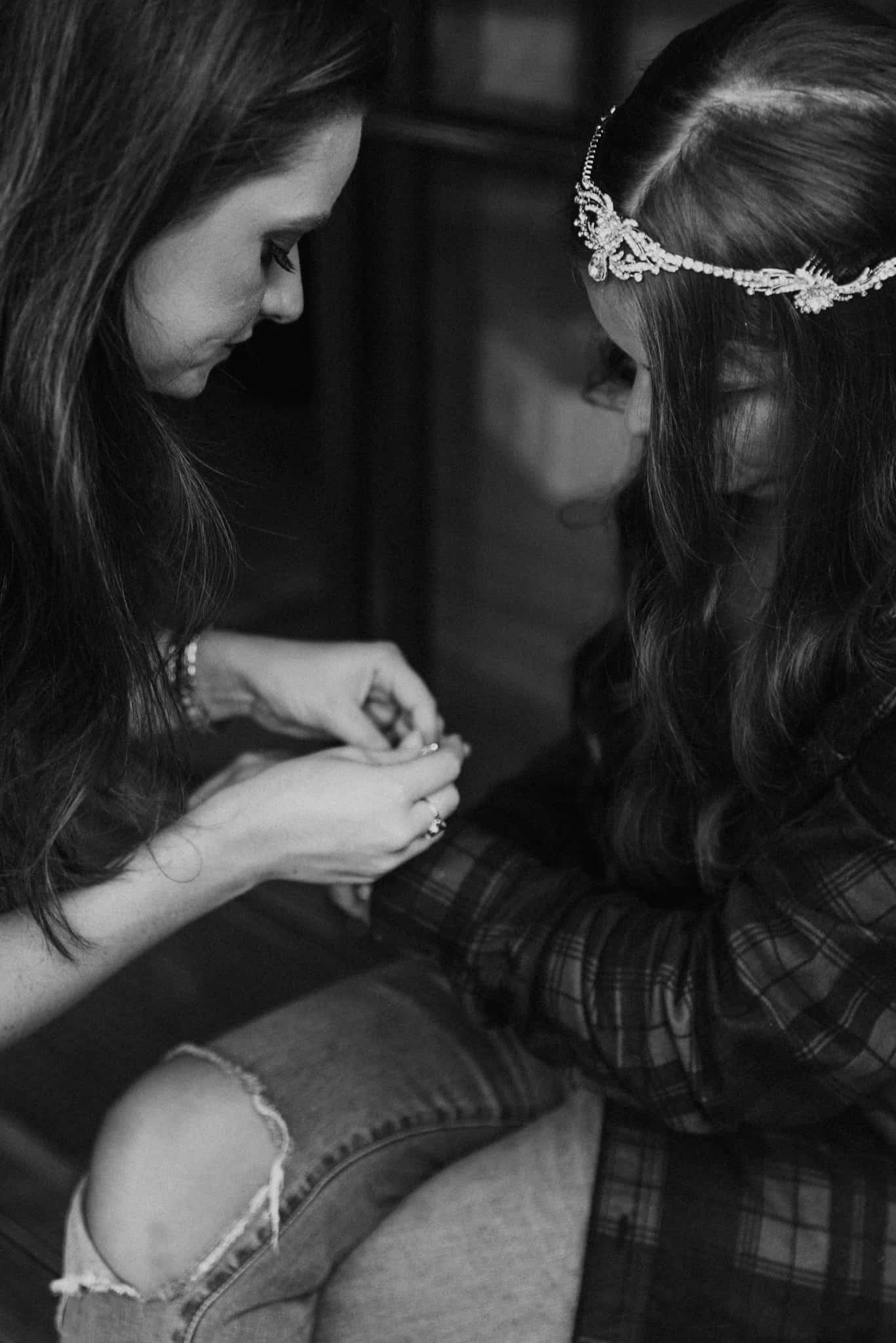 Friend helps bride put on bracelet Captured by James White Hunter Valley Wedding Photographer
