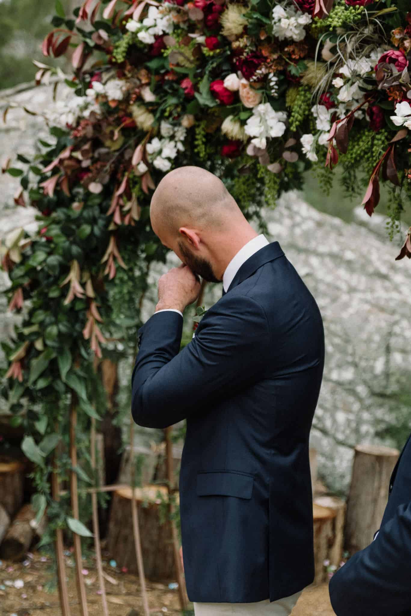 Groom tears up in front of large floral arbour as he sees his bride Captured by James White Hunter Valley Wedding Photographer