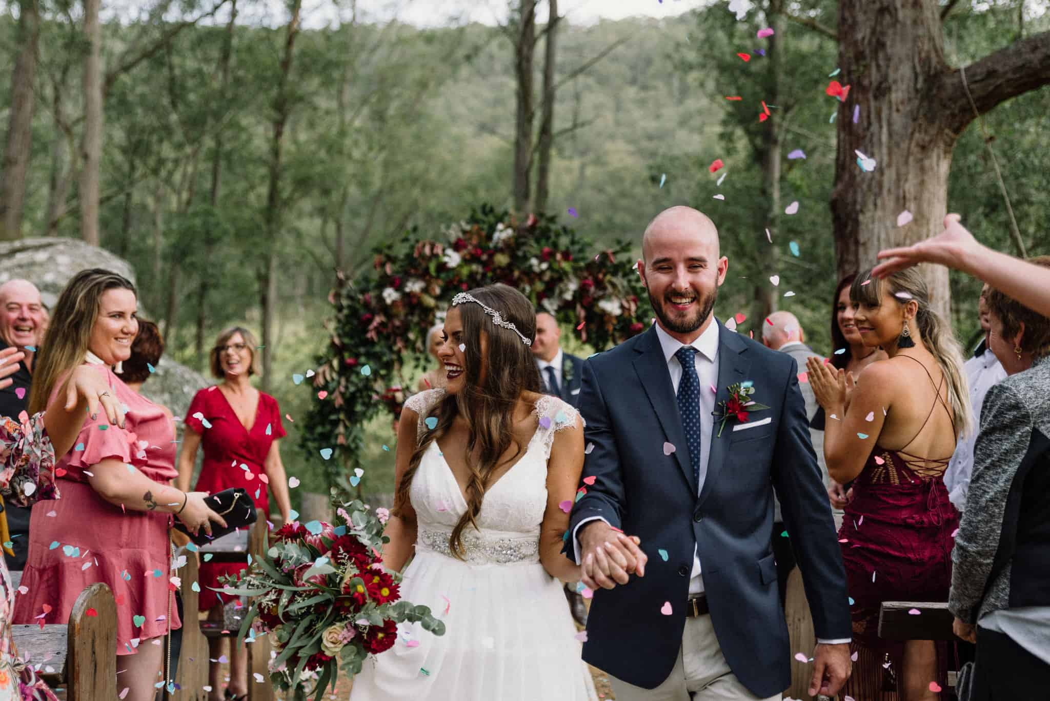 Couple hold hands as friends throw confetti to celebrate newlyweds Captured by James White Hunter Valley Wedding Photographer