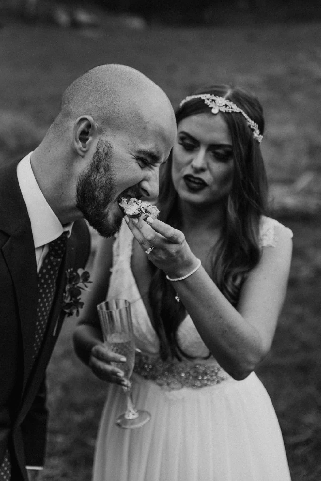 Bride holds champagne as she feeds groom wedding cake Captured by James White Hunter Valley Wedding Photographer