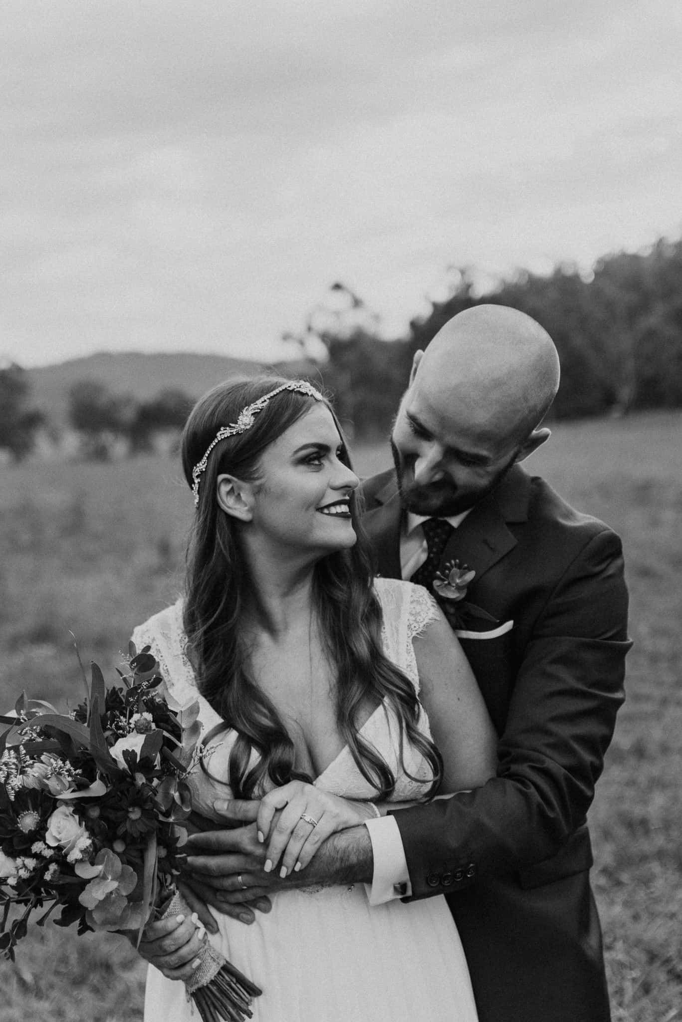 Bride looks back at groom during cute sunset photos Captured by James White Hunter Valley Wedding Photographer