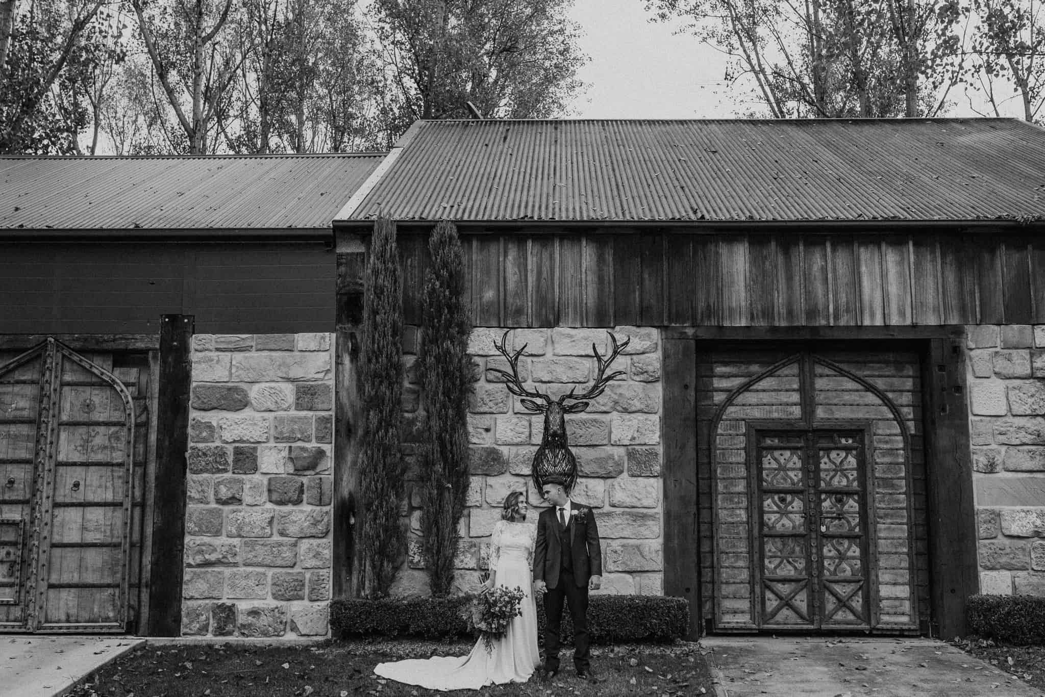 beautiful bride and groom standing out front of stonehurst cedar creek big wooden doors james white hunter valley wedding photographer