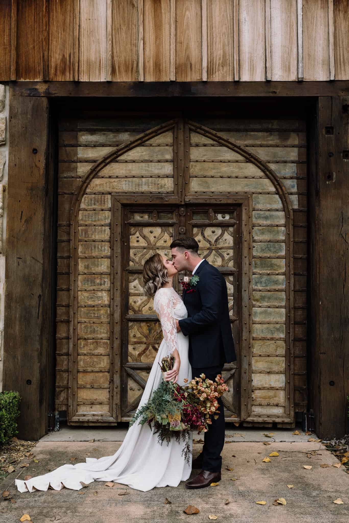 Stunning bride and groom kiss in front of old wooden door at stonehurst cedar creek james white hunter valley wedding photographer