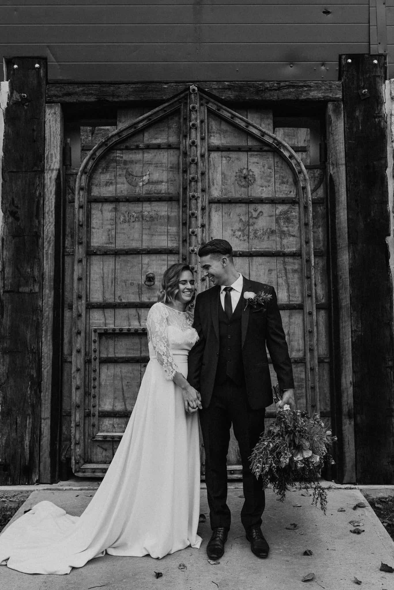 bride and groom laughing as they hold hands in front of blue wooden door at stonehurst cedar creek james white hunter valley wedding photographer