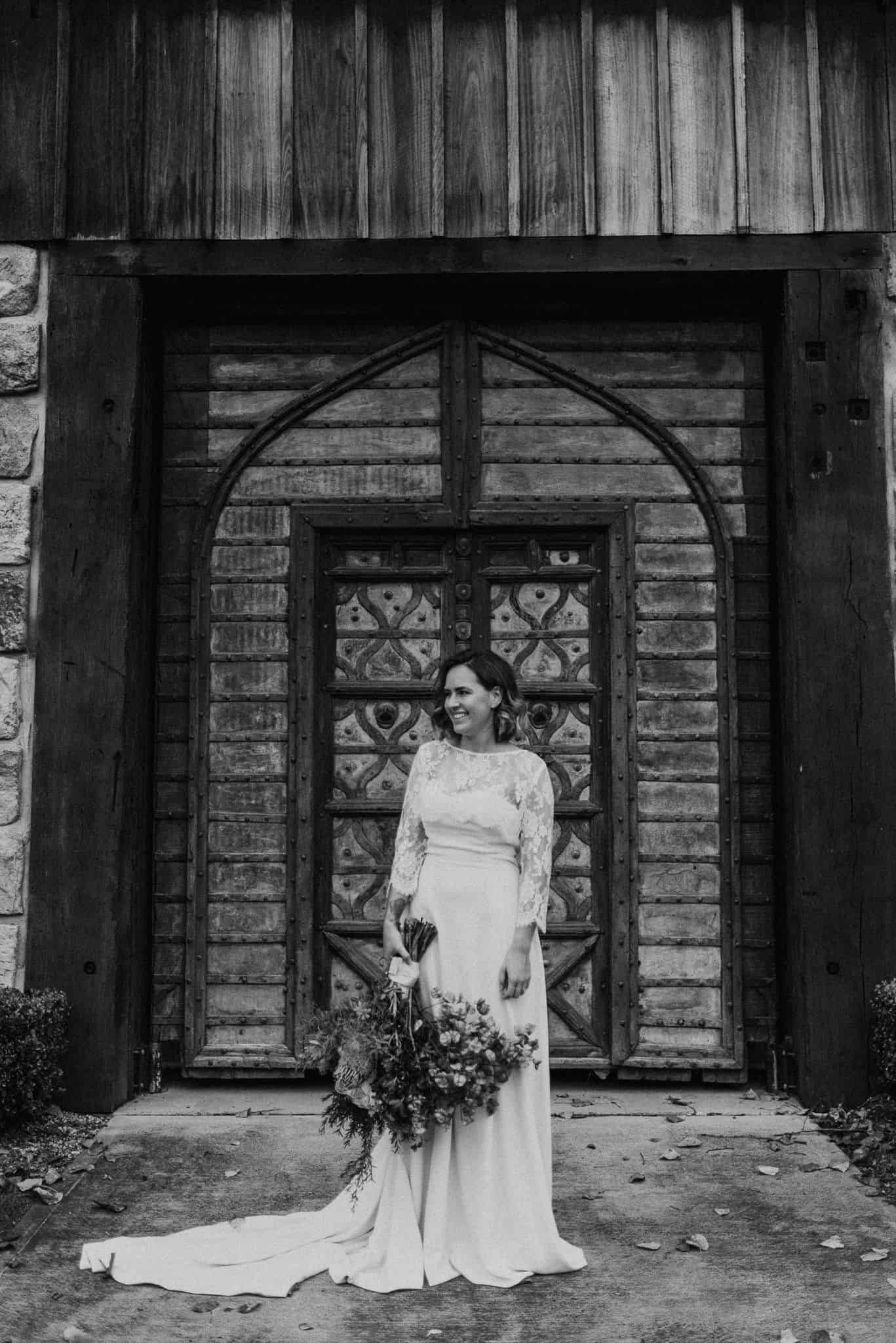 bride standing out front of stonehurst cedar creek holding beautiful natives bouquet james white hunter valley wedding photographer