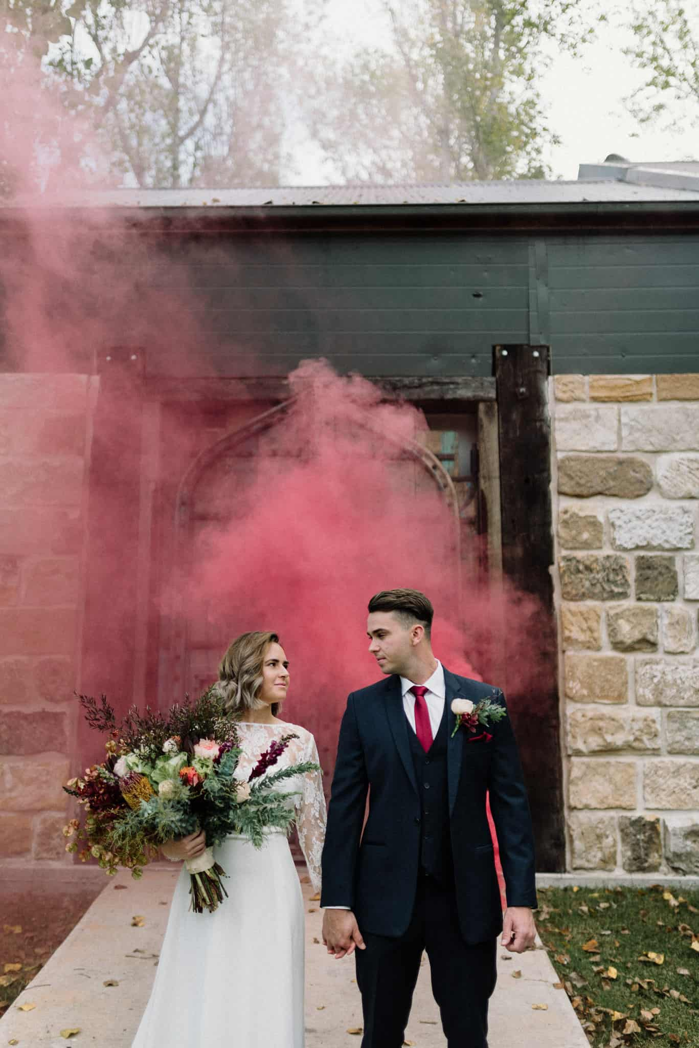 gorgeous shot of bride and groom at stonehurst cedar creek, gazing into each others eyes as pink smoke bomb sets off behind them james white hunter valley wedding photographer