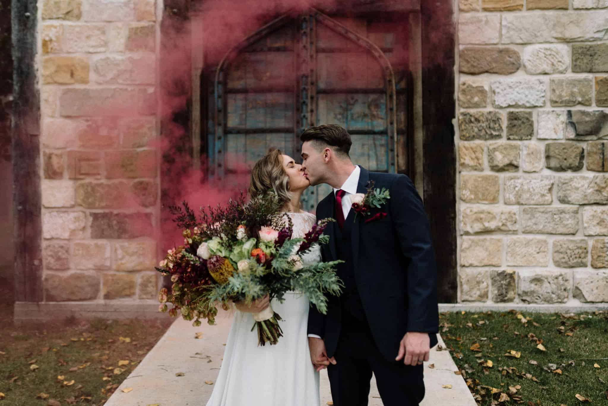 bride and groom first kiss as red smoke engulfs them at stonehurst cedar creek james white hunter valley wedding photographer