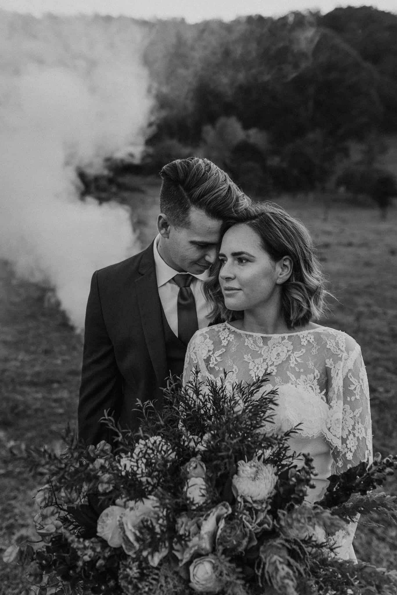 gorgeous bride and groom stand in open field with smoke bomb blowing behind them james white hunter valley wedding photographer