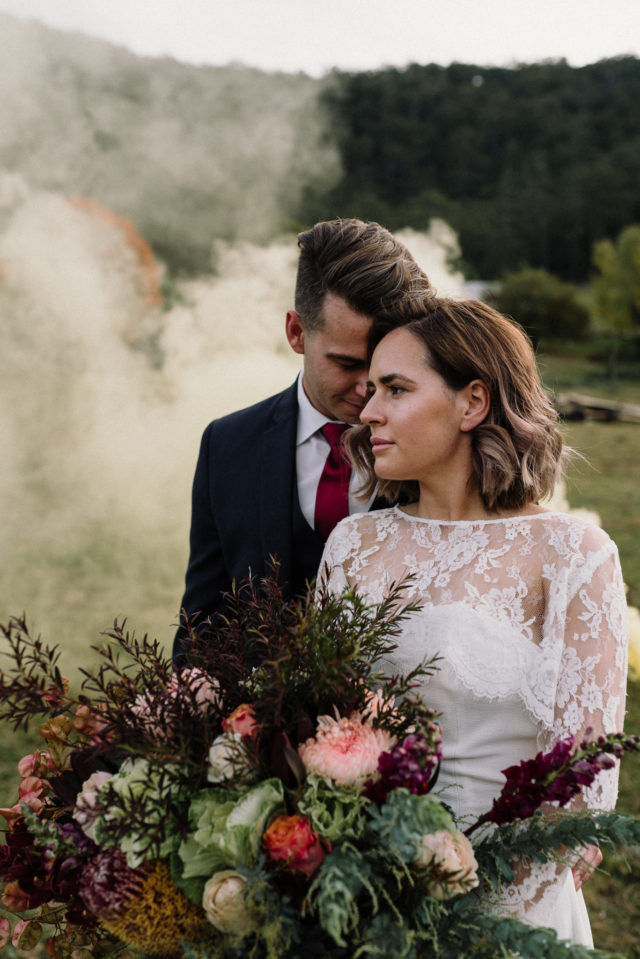 eloping vs wedding bride and groom embrace in a hunter valley field with smoke bomb behind them