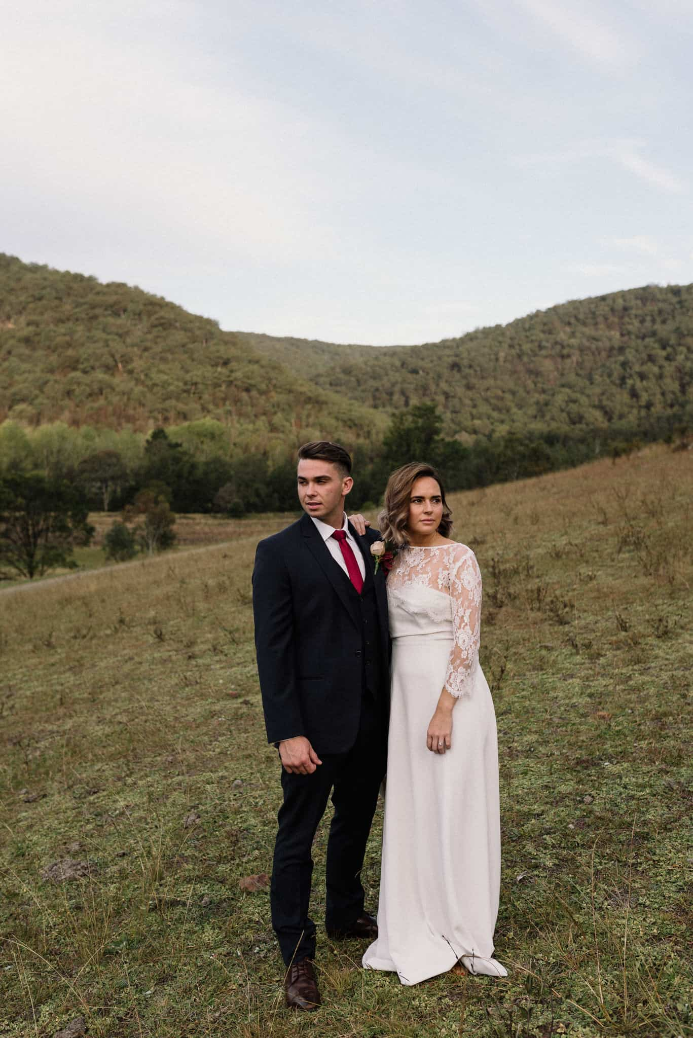 bride and groom standing on the side of a mountain behind stonehurst cedar creek james white hunter valley wedding photographer