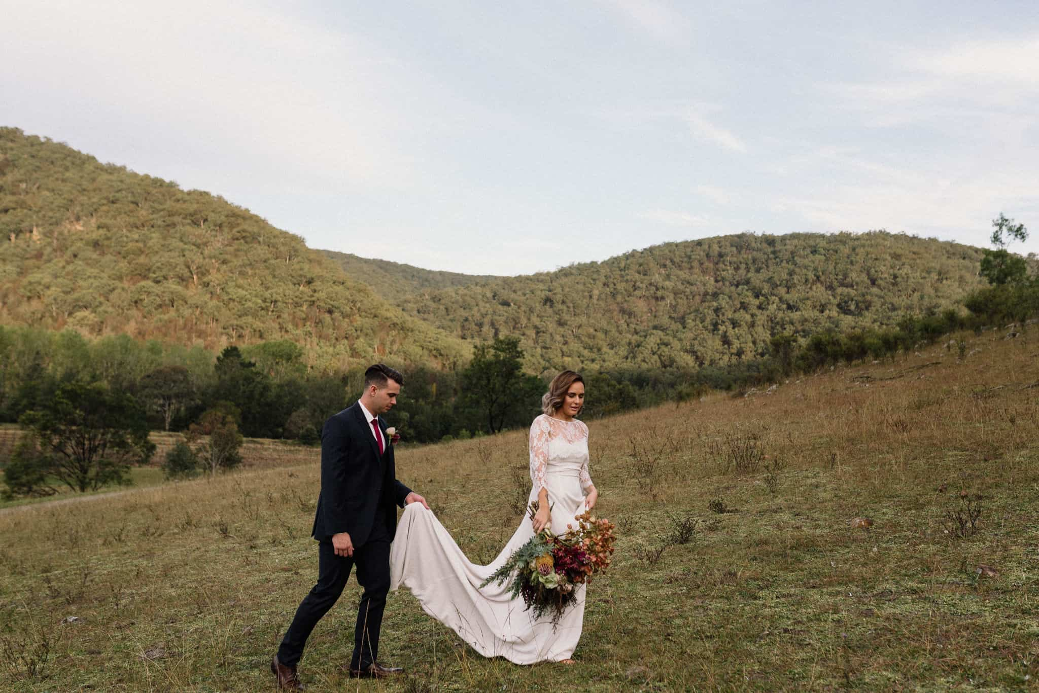 bride and groom walking up the side of a mountain, covered in rocks at stonehurst cedar creek james white hunter valley wedding photographer