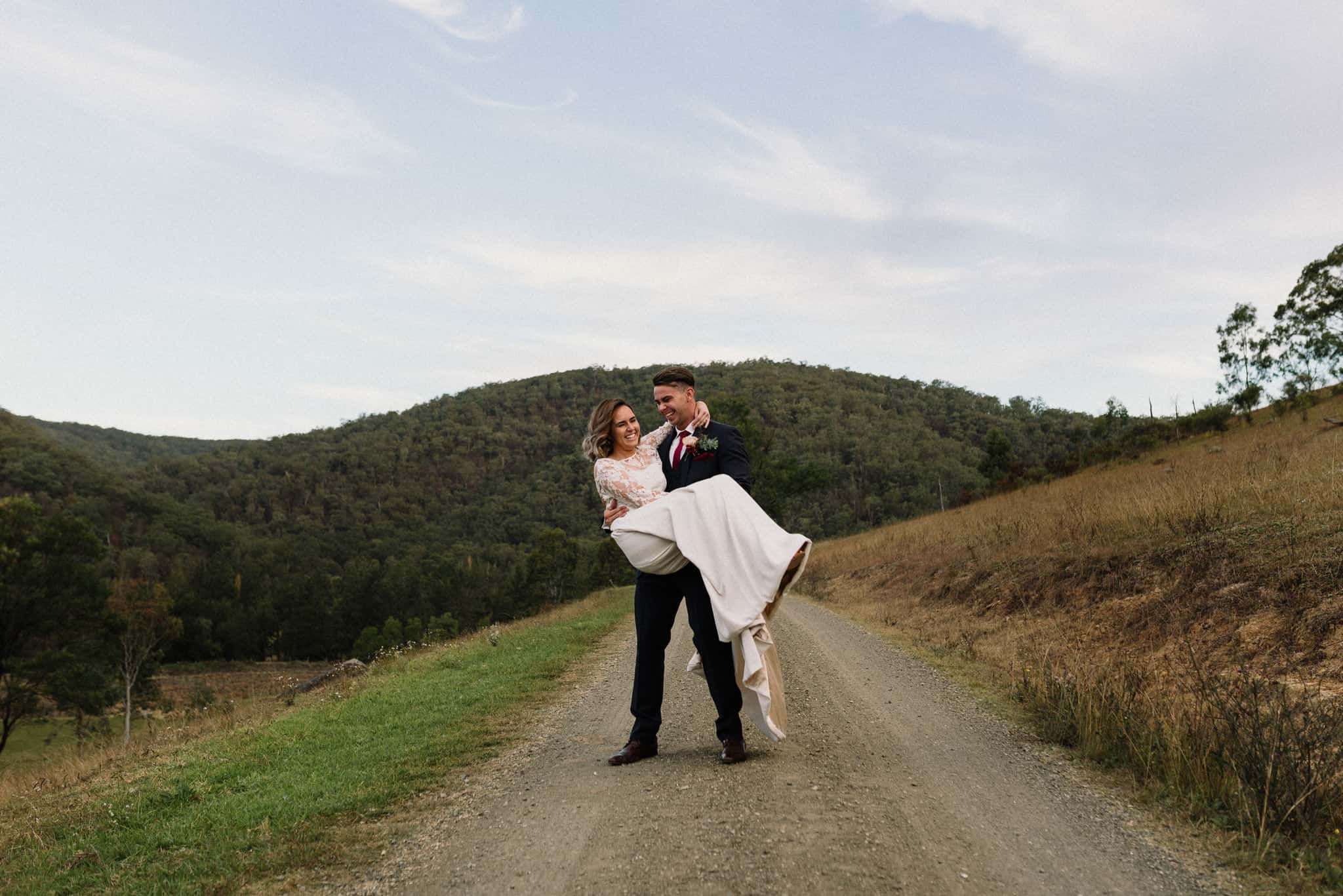 groom picks up bride and spins with her on a country dirt road at stonehurst cedar creek as they laugh james white hunter valley wedding photographer