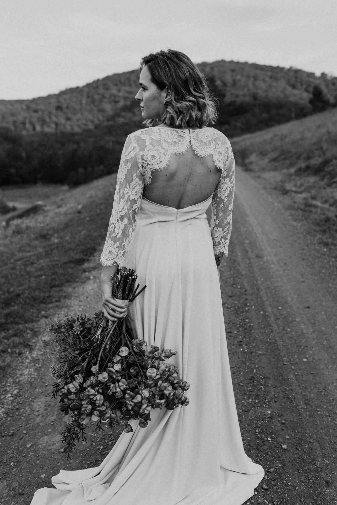 bride stands on dirt road at stonehurst cedar creek as she looks into the valley. Beautiful detail of wedding dress james white hunter valley wedding photographer