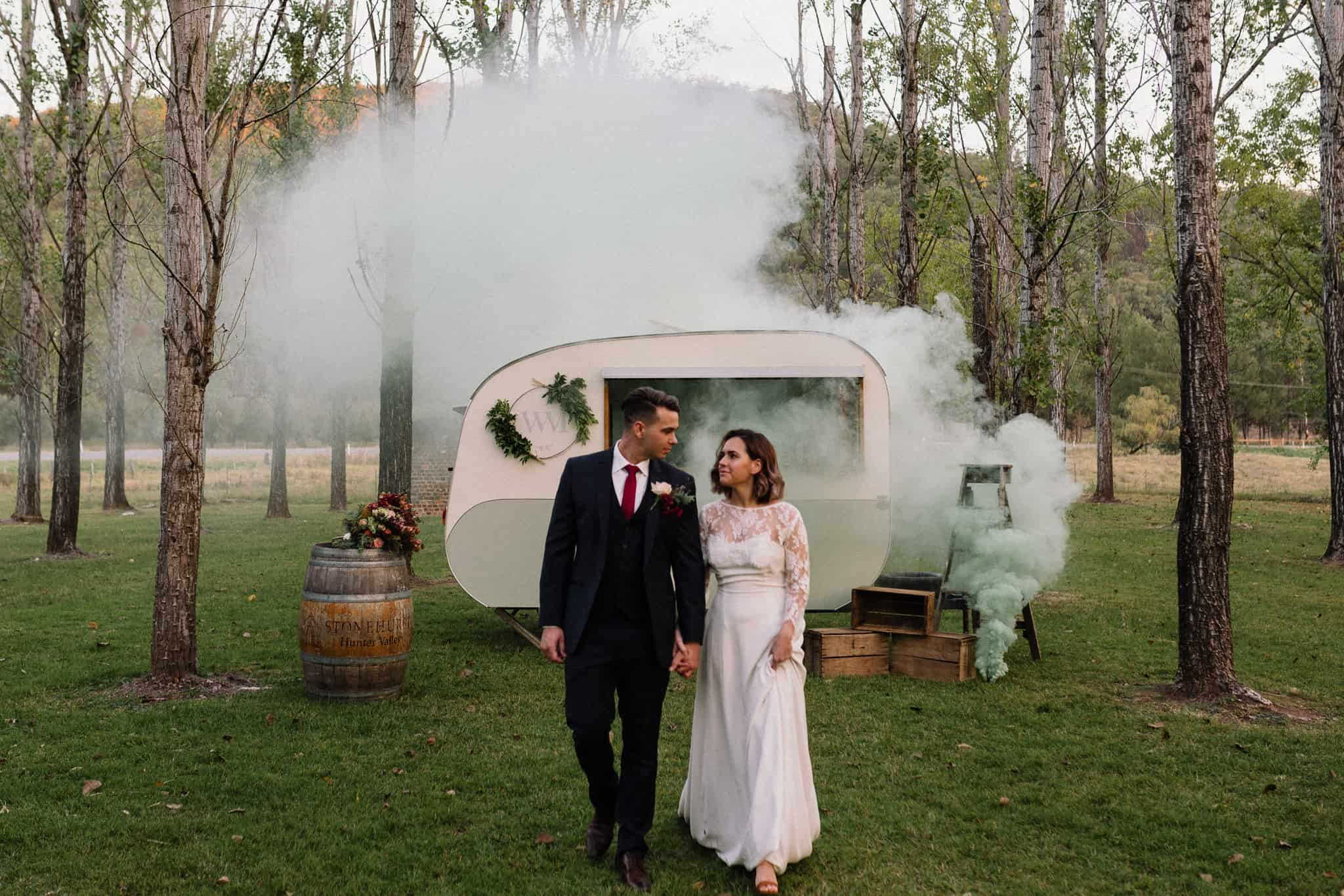 bride and groom walk through rows of trees, as a green smoke bomb engulfs caravan bar behind them james white hunter valley wedding photographer